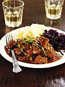 Wild boar and beer stew with mashed potato and red cabbage