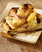 Bread and butter pudding on a plate with a spoon