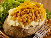 A baked potato with baked beans and Cheddar cheese