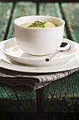 Pea soup with chives in a bowl on wood