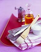 Various utensils: tongs, brush, salt, peppermill, oil