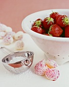 Fresh strawberries in a colander, meringues, icing sugar