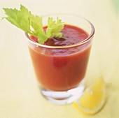 A glass of Bloody Mary with celery and lemon