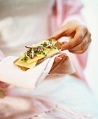 Woman holding crispbread with cheese and onion on fabric napkin