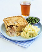 Chicken and ham pie with mashed potato and peas