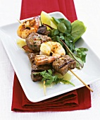 Barbecued beef and prawn kebabs with salad leaves