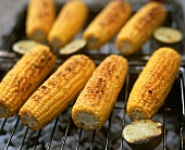 Corn on the cob and lime halves on barbecue