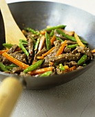 Beef and vegetables with sesame seeds in wok