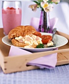 Croissant filled with ham and scrambled egg on a tray