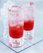 Red cocktails with soda water over ice