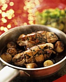 Turkey roulade with pearl onions in a pan