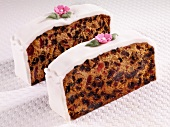 Two slices of fruit cake with white icing