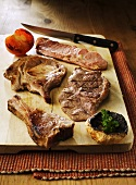 Assorted grilled steaks and chops on chopping board
