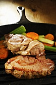 Wild boar steaks with vegetables in grill pan