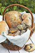 Assorted breads and rolls in a basket on a garden table