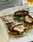 Grilled aubergine slices with halloumi on caraway crostini