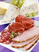 Cold cuts platter with olives and cheese board with grapes