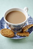A cup of tea with milk and ginger biscuits