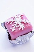 Petit four with pink icing and snowflake decoration