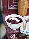 A bowl of borscht with sour cream