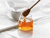 Honey in a jar and on a honey dipper