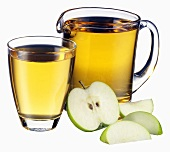 Apple juice in jug and glass and pieces of apple