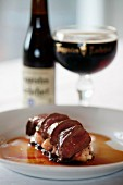 Venison loin fillet on red wine sauce & a glass of dark beer
