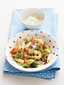 Penne with prawns, broccoli and cheese in spotted dish