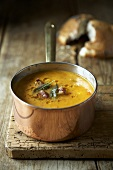 Pumpkin soup with sage and bacon in copper pan