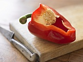 Red pepper with a section removed on chopping board