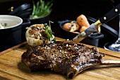Beefsteak on chopping board, garlic, carrots