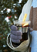 A hand holding a glass of mulled wine