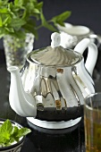 Silver teapot with glass of mint tea