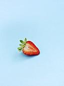 Half a strawberry on blue background