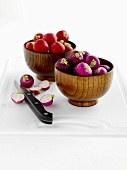 Radishes in wooden bowls on chopping board