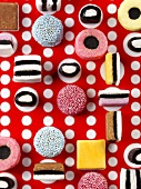 Liquorice allsorts on red and white patterned background