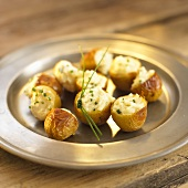 Small baked potatoes with chives on pewter plate