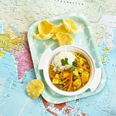 Fruity chicken curry on tray on map (India)