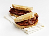 Bacon sandwiches on fabric napkin