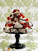 Meringues with chocolate sauce, berries, cream & nuts on cake stand