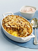 Peach crumble with flaked almonds in baking dish