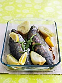 Baked trout with artichokes in glass baking dish