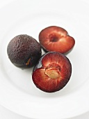 A whole plum with two plum halves