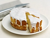 Lemon cake with icing, partly sliced