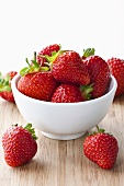 Fresh strawberries in and beside bowl