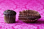 Chocolate muffin and empty paper cases