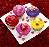 Plate of muffins decorated with hearts on rose petals