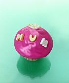 A muffin with pink icing and the word MUM
