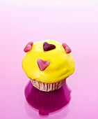 Muffin with yellow icing and fruit jelly hearts