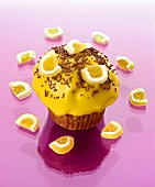 Muffin with yellow icing, chocolate vermicelli & jelly sweets